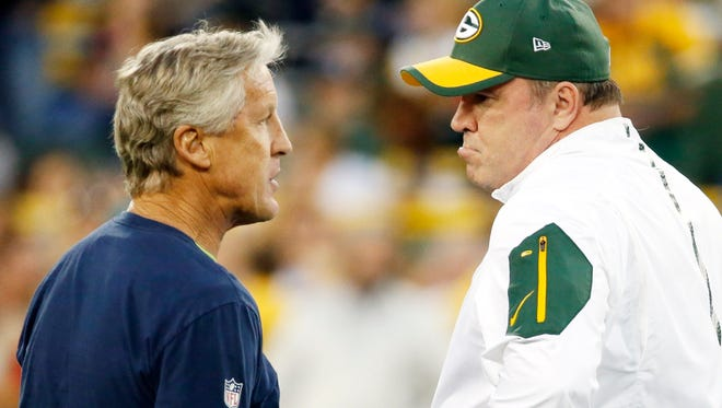 Seattle Seahawks head coach Pete Carroll, left, talks to Green Bay Packers head coach Mike McCarthy before an NFL football game Sunday, Sept. 20, 2015, in Green Bay, Wis.