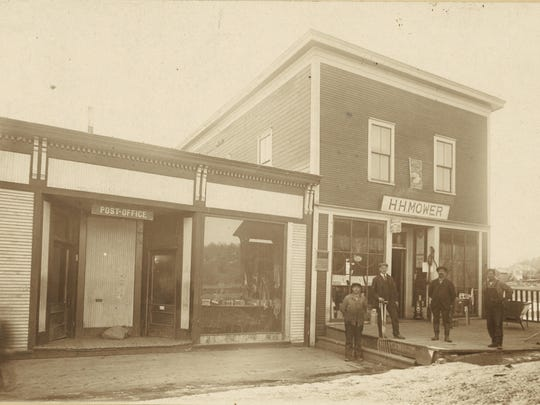 Photo shows the H.H. Mower store, which was a hardware store on Bridge Street next to Black Creek. Next to it on the left is the Post Office tended by Mamie Marsh and in the window of the building are books consistent with the library housed there at that time. He built this business up consistently through displays at the Sheldon Fair and by providing area farmers with consistently good workmanship on plumbing. In 1927 the Great Flood inundated his shop with some 11 inches of water destroying much of his inventory. He remained in business at this location until 1932.