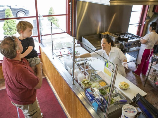 """John Kelly holds his 2-year-old son Colin as Martha Rodriguez prepares their food at the Michoacana Grill in Kennett Square Kelly was stopping at the restaurant for the first time. """"I drive buy the place all the time,"""" he said. """"If one more person told me I need to eat here..."""""""