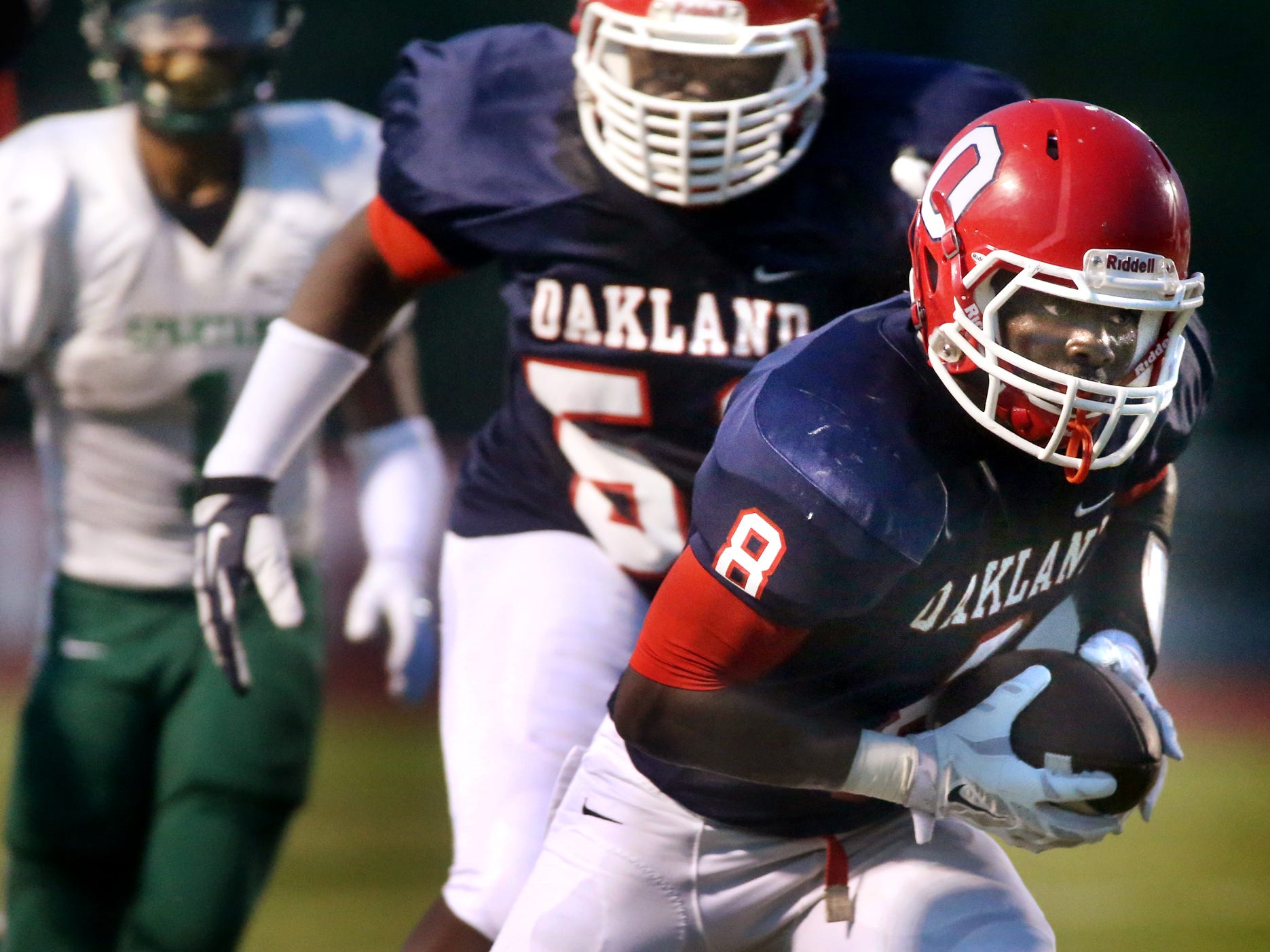 Oakland's George Gbesee picks up a fumble and runs it in for a touchdown in the first half of the game against White Station at Oakland, on Friday, August 2, 2014.