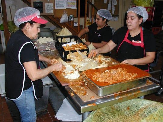 Hand filling and rolling tamales are, from left, Maria Salamanca, Romelia LeDesma and Yuri Navarro.