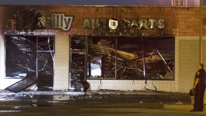Police stand watch over the burned out remains of an O'Reilly Auto Parts store, early Sunday, Aug. 14, 2016, near N. 35th Street and W. Burleigh Street in Milwaukee. After a police officer shot and killed an armed suspect after a foot chase, a gas station, a beauty supply store, a bank and an auto parts store were set ablaze in violence related to the shooting. (Mark Hoffman/Milwaukee Journal-Sentinel via AP)
