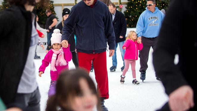 Parents hold their children's hands while skating at Knoxville's Holiday On Ice in Market Square. Knoxville's Holidays on Ice, presented by Home Federal Bank, will be open through Jan. 8.