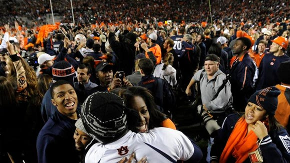 Fans swarm the field after Auburn defeated Alabama in the Iron Bowl at Jordan-Hare Stadium. (Mickey Welsh, Montgomery Advertiser)