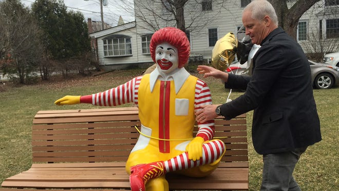 Ken Coleman of St. Louis, Missouri helps set up a Ronald McDonald statue at its new home in Burlington on Tuesday. Coleman brought the statue from his home in Missouri to Burlington after the former statue was vandalized.