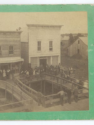 A photo shows a section of the Little Falls ravine near O. L. Clyde's store at the corner of Broadway and Second Street Northeast in Little Falls, the current location of Pete &Joy's Bakery. Photo by Neal & Simmons, ca. 1883-1885.