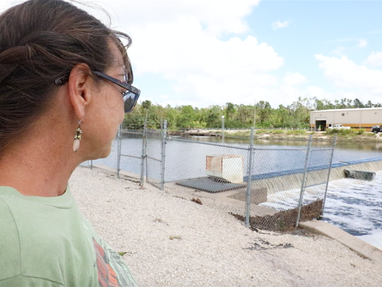 Anita King, owner with husband Tom of Cambird Auto Body on Old 41, stands by a weir at the end of her road that was buried in floodwaters during the Southwest Florida rains of August and  September's Hurricane Irma. King and other flood victims think the weir may have played a role in the canal's failure to protect them. They wonder why, when Lee County added 20 square miles of airport lands to the canal's conveyance load, it didn't also improve the weir.