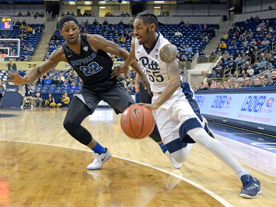 Pittsburgh guard Jonathan Milligan (55) drives around Buffalo guard Dontay Caruthers (22) during the first half of an NCAA college basketball game, on Dec. 7, 2016. Caruthers was the 2014 All-Greater Rochester Player of the Year for East High.
