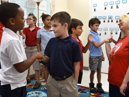 """Second grade students Aiden Flores (left) and Wyatt Russell (center) take part in the Brain Smart Start program morning greetings at the start of Courtney Antosh's class Tuesday, Nov. 14, 2017, at Indian River Academy in Vero Beach. """"We can improve kid's lives, help them be more academically prepared for the next year, also socially and emotionally engaged with their peers,"""" said literacy coach Kim Smith (right)."""