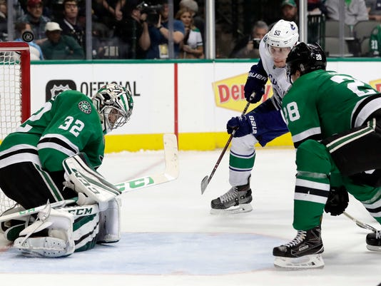 Dallas Stars goalie Kari Lehtonen (32) deflects a shot over his head from Vancouver Canucks center Bo Horvat (53) as defenseman Stephen Johns (28) watches in the second period of an NHL hockey game in Dallas, Sunday, March 25, 2018. (AP Photo/Tony Gutierrez)