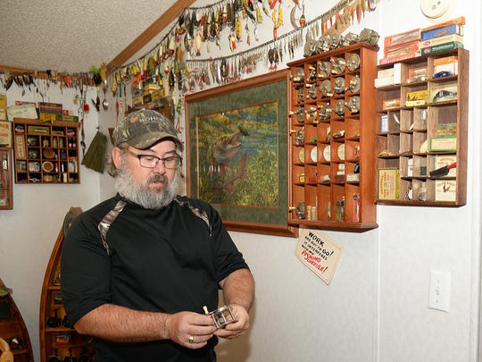 Jim Fritz inspects a 1920s-era fishing reel at his