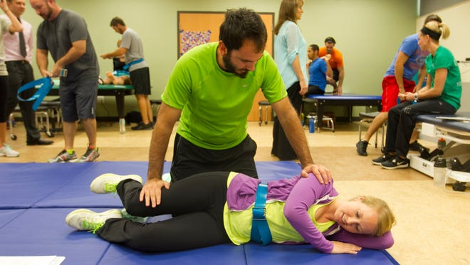 Raymond Agostino and Erin Pauley, both graduate physical therapy students, practice exercises for amputees on Thursday at FGCU.