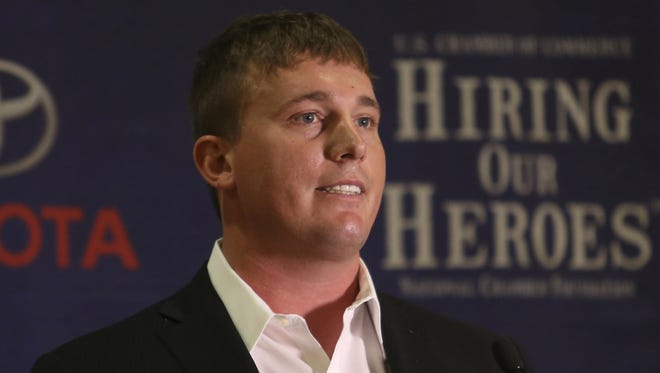 Medal of Honor recipient Dakota Meyer talks to the crowd at a Veterans Job Fair in Louisville, Ky., on Friday, Feb. 21, 2013. Veterans with a significant public profile, such as Meyer, can either bridge or widen the gap between military and civilians.