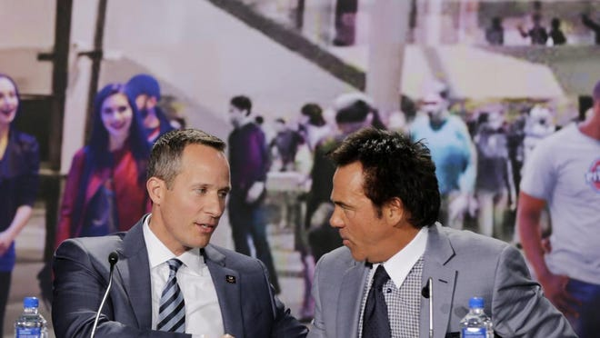 Tom Gores, right, shakes hands with Christopher Ilitch during a press conference on Tuesday in Detroit.