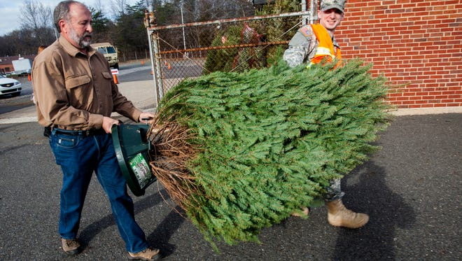Sgt. Paul Richter (right) 250th Brigade Support Battalion, New  Jersey Army National Guard, and Tim Dunne of  New Jersey Christmas Tree Growers Association carry a Christmas tree inside the Joint Military Family Assistance Center, Bordentown, N.J., for the Christmas Trees for New Jersey Military Families event
