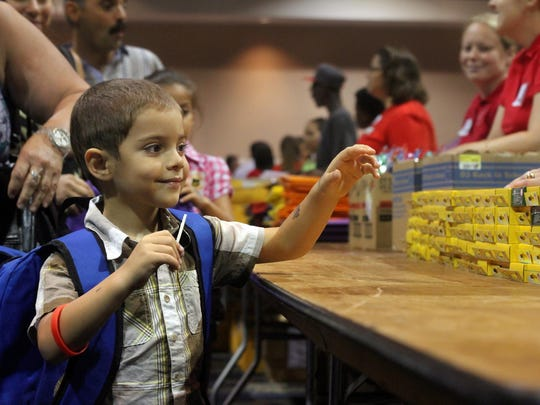 Eric Bahamonde collects crayons during the Back-to-School Supply Giveaway and Festival in 2012 at the Harborside Event Center in Fort Myers.
