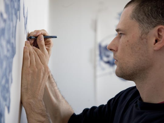 Artist Derek Lerner is shown working in his studio.