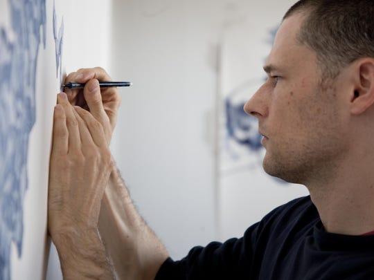 Artist Derek Lerner is shown working in his studio.