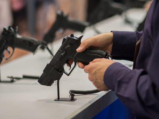 Man looking at pistol at gun show