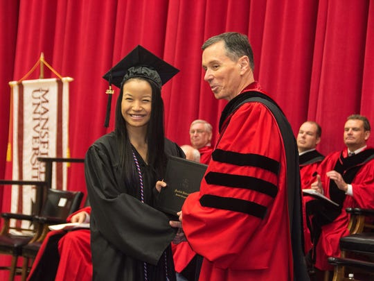 Mansfield University President Fran Hendricks presents Aria Worthington of Mansfield with her diploma for a bachelor of science in business administration.