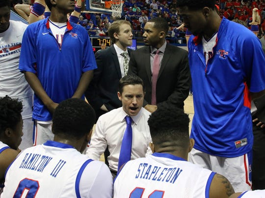 Louisiana Tech basketball coach Michael White huddles with his team.