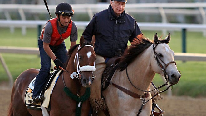 Mr. Z, ridden by exercise rider Edvin Vargas, trots along trainer D. Wayne Lukas as the Preakness Stakes entrant goes to the track for a workout at Pimlico Race Course in Baltimore, Thursday, May 14, 2015.  (AP Photo/Garry Jones)