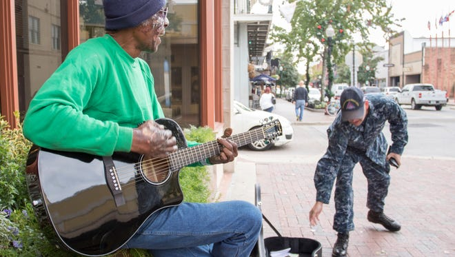 """Despite being burned by the fire that consumed his home and all of his belongings, street musician Maurice Sorrell continues his daily performances on Palafox St. in Pensacola, FL on Thursday, December 8, 2016.  The """"Maurice Fire Recovery Fund"""" that was set up for Sorrell at GoFundMe.com/p/jbykm has already surpassed its original modest goal of $1,500 and continues to grow in an effort to start replacing all that he has lost and to help Maurice get back on his feet."""