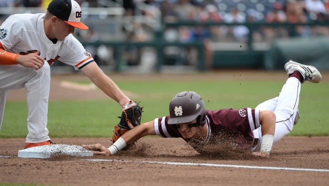 Jun 22, 2018; Omaha, NE, USA; Mississippi State Bulldogs center fielder Jake Mangum (15) slides in ahead of the tag of Oregon State Beavers first baseman Zak Taylor (16) on a pick off attempt in the first inning in the College World Series at TD Ameritrade Park. Mandatory Credit: Steven Branscombe-USA TODAY Sports