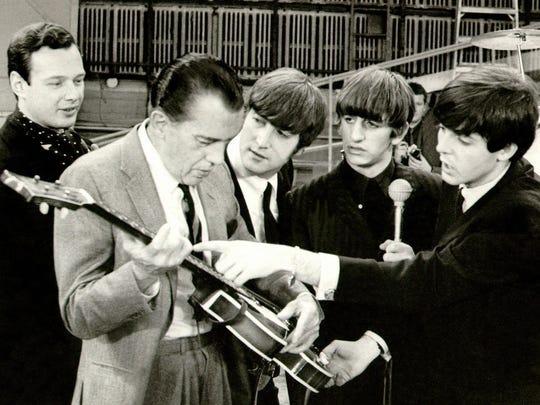 Brian Epstein looks on as the Beatles show Ed Sullivan a guitar.