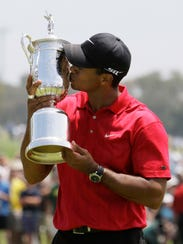 Tiger Woods kisses his U.S. Open championship trophy