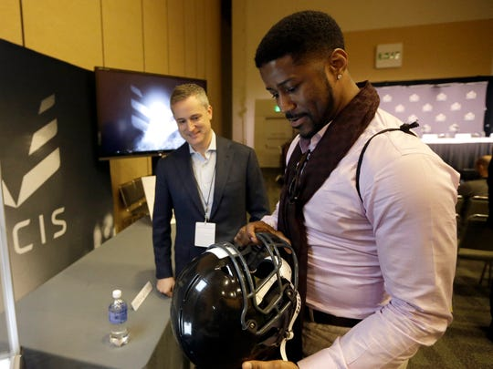 Former NFL football player Nate Burleson, right, looks at the Vicis Zero1 football helmet as he talks with Vicis Chief Executive Officer and co-founder Dave Marver before an NFL health and safety news conference Thursday, Feb. 4, 2016, in San Francisco.