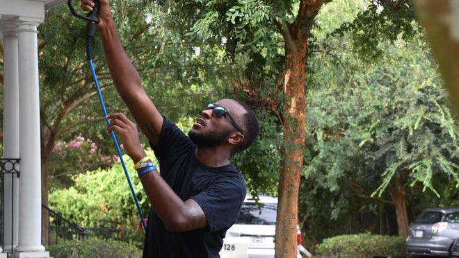 Malachi Stewart, a member of Phi Beta Sigma fraternity, power washes the Family Promise Day Center building.
