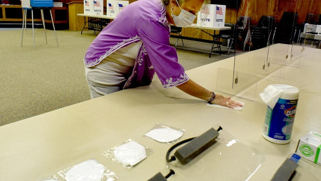 """Frenchtown Township voter registration specialist Mary Kittle wipes down the tables Monday as they get ready for the primary election today. """"We have ten voting stations as of now,"""" said Frenchtown Clerk Kyle Bryant."""