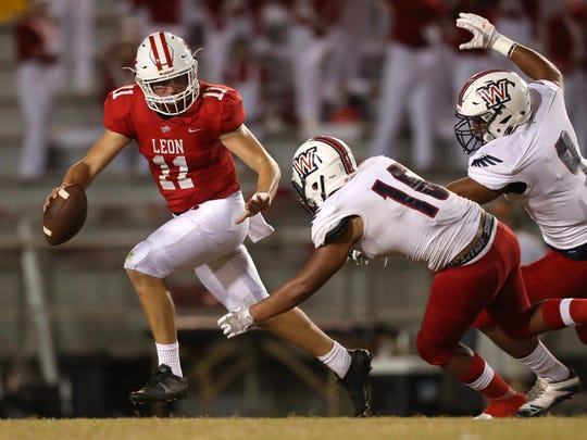 Leon's John Carey tries to escape Wakulla's Kameron Burns (9) and Tommie Webster (16) during their game at Cox Stadium on Thursday night.