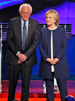 Democratic presidential candidates  Sen. Bernie Sanders, of Vermont, left, and Hillary Rodham Clinton talk before the CNN Democratic presidential debate Tuesday, Oct. 13, 2015, in Las Vegas.