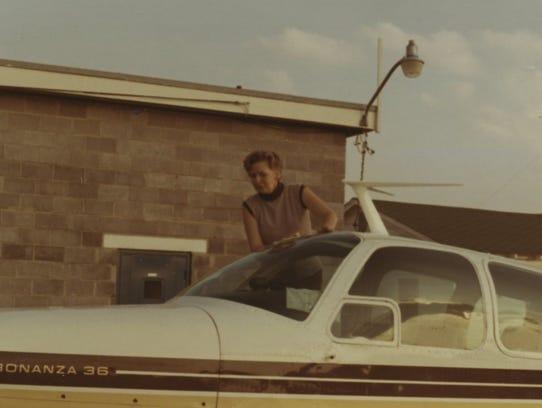 Lois Chapin Moore climbs into the private Bonanza aircraft