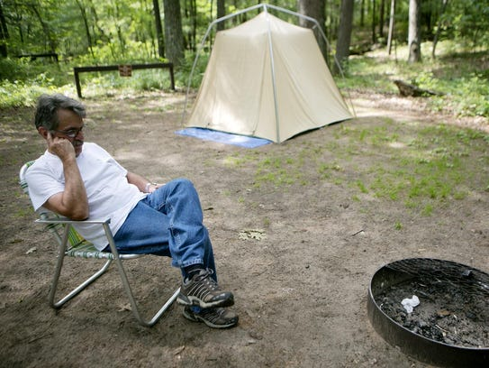 Ron Standish of Madison watches his fire die at a campsite
