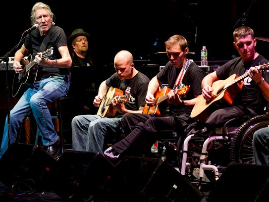 Roger Waters, left, performs with injured service members
