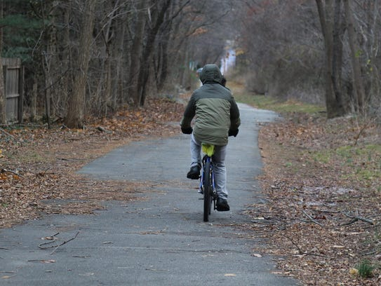 A cyclist riding down the path in Ramsey in the late