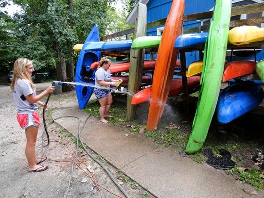 Abby Weston, left. and Megan Faulkner clean kayaks