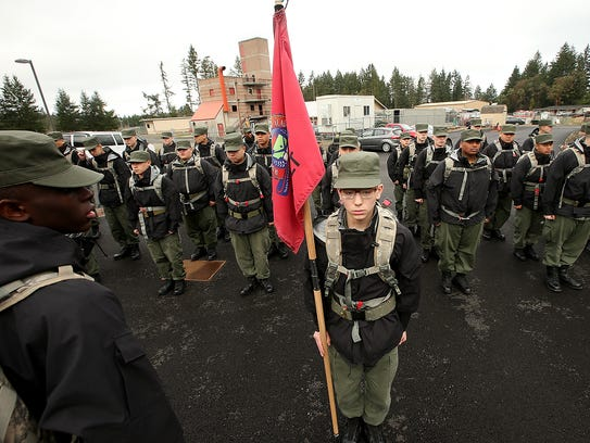 Washington Youth Academy cadet Tyler Sexton, center, carries the First Platoon Wolf Pack flag as cadets get ready to march in formation to the mess hall on Thursday.