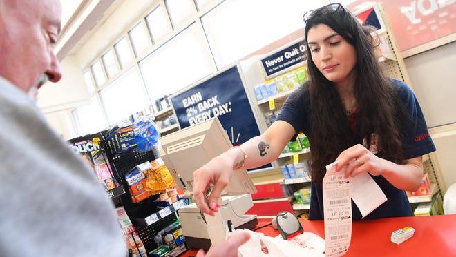 CVS employee Kaylee Merrick, 24, works the register at her store in Stafford, Va.