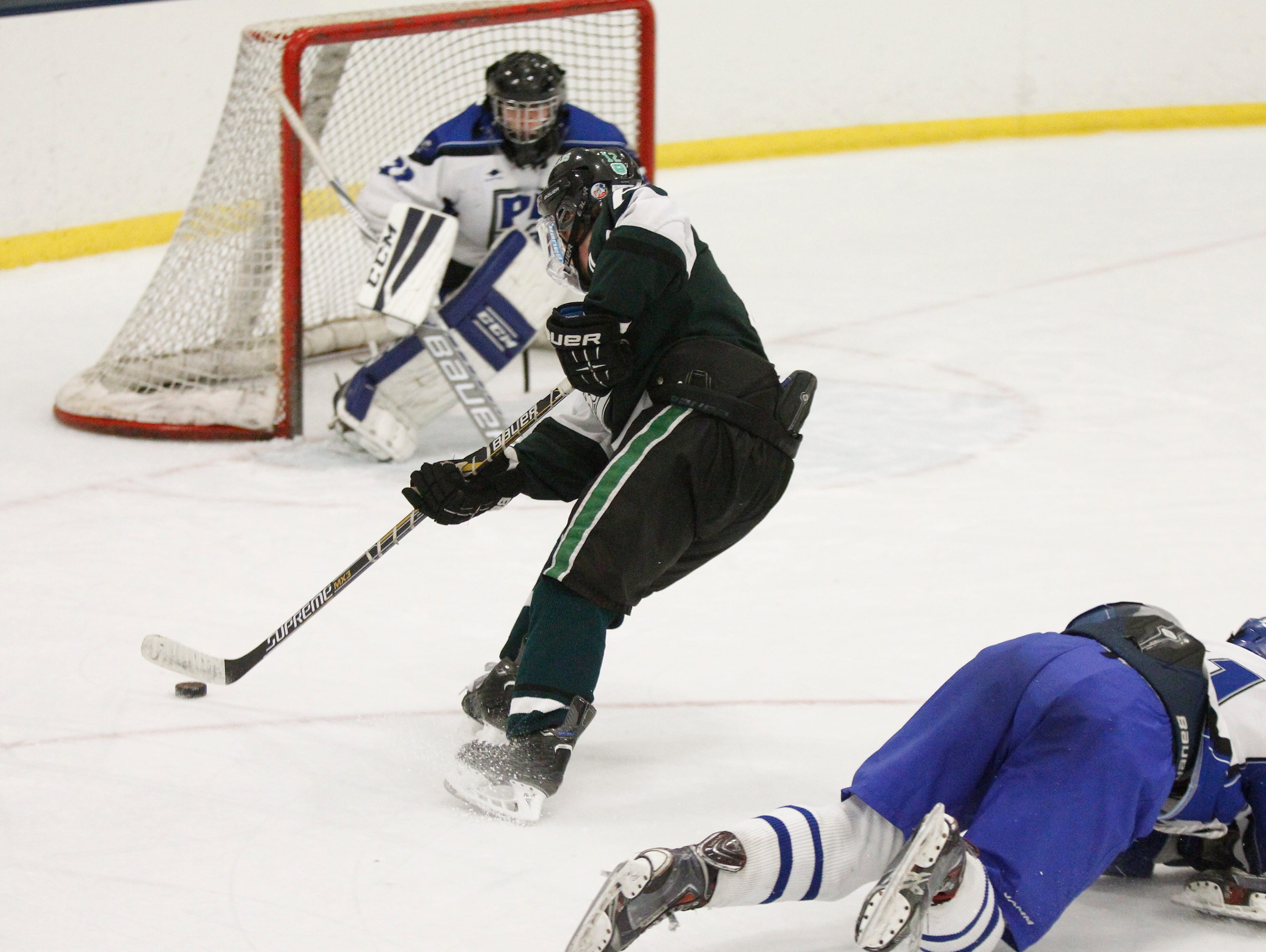 Brewster's Jason McNamara (12) puts a backhand shot on Pearl River goalie Darragh Keetley (32) during their 4-4 overtime tie game at Sport-O-Rama in Monsey on Saturday, Jan. 9, 2016.