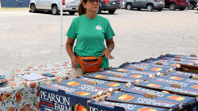 """Kim Sparks with the Georgia Peach Connection counts boxes of fresh Georgia Peaches being unloaded at Belle Starr Antiques, 410 N. B., Friday, July 3, 2020, for pre-order pick-up and host site sales. Sparks said that the """"1,000 or so, 25-pound boxes of peaches,"""" were harvested Tuesday, June 30, and since delivered throughout Northwest Arkansas with 70 boxes pre-ordered in Fort Smith."""