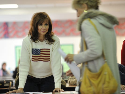 A woman checks in voters during a Republ