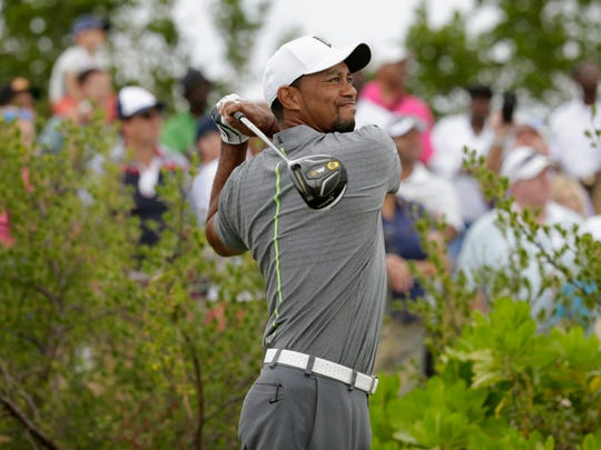 Tiger Woods watches his tee shot during the third round at the Hero World Challenge golf tournament December 3 in Nassau, Bahamas. It was Woods' first tournament in over a year.