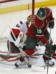 Ottawa Senators goalie Craig Anderson knocks a shot away from the Minnesota Wild's Jason Pominville, right, in the first period on March 31 in St. Paul.