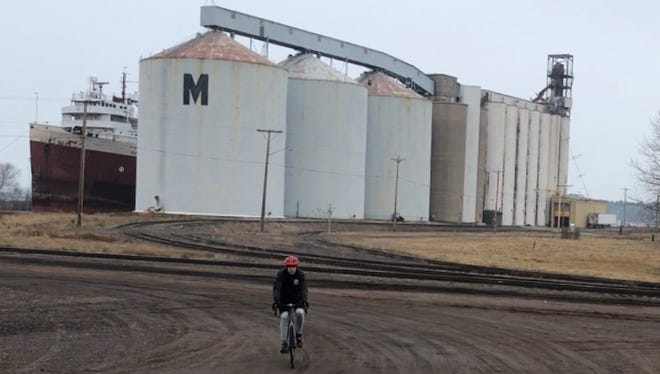 Mark Nicklawske rides near the Osaugie Trail in Superior, which runs along the docks of Superior Bay.