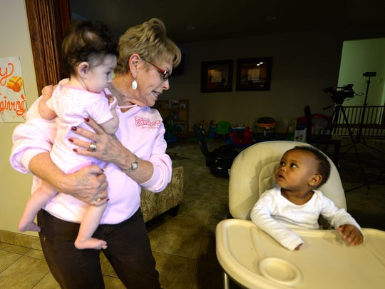 House of Hope volunteer JoAnn DeVoe interacts with two of the infant residents of the shelter November 24, 2014.
