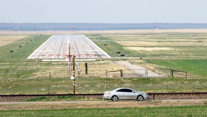 A car drives past the end of an 8,000-foot-long runway at Front Range Airport outside of Denver on April 30, 2018. The airport's managers hope to become Spaceport Colorado by the end of the year.